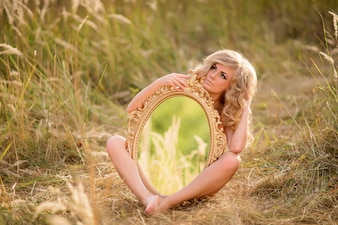 Blonde naked woman holds a mirror sitting on the grass in the field