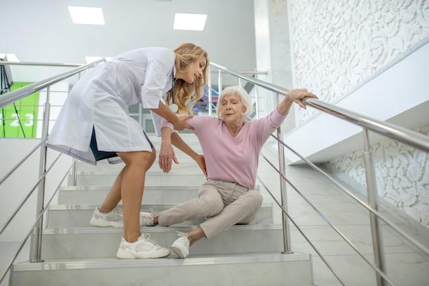 Блондинка медсестра помогает пожилой женщине, которая упала на ремнях