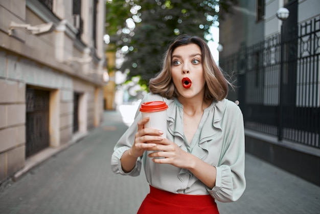 Blonde outdoors red skirt hot drink outdoors in summer. high quality photo