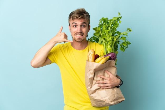 電話のジェスチャーを作る青い背景で隔離の持ち帰り用食品の袋を取っている金髪の人。コールバックサイン