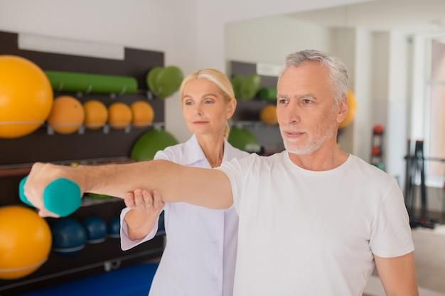 トレーニング中に男性患者を支援する金髪の理学療法士