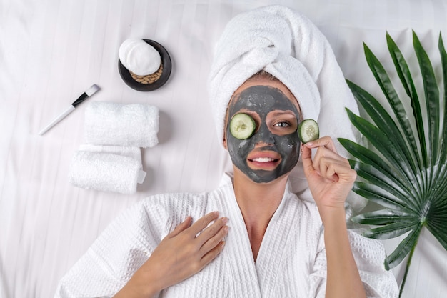 The blonde poses in a towel on her head posing with a clay mask on her face and a cucumber on one eye and the other in her hand