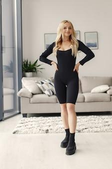 금발 포즈. 검은 양복을 입은 아가씨. 집에서 여자.