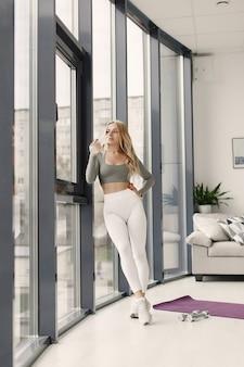 金髪のポーズ。スポーツスーツを着た女性。窓際の家にいる女性。
