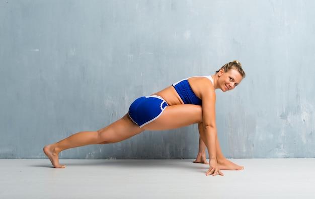 Blonde pregnant woman doing yoga
