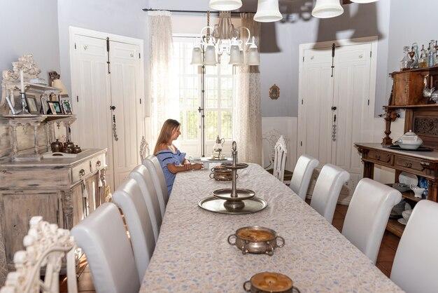 彼女の家の窓の外を見ている青いドレスを着た金髪の妊婦。彼女の家の広い居間に座っている。