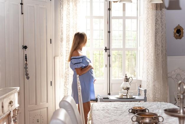 그녀의 집 창 밖을 찾고 파란 드레스에 금발 임신한 여자.