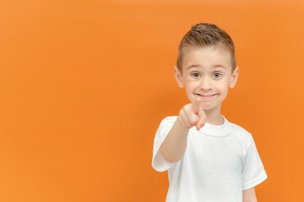 주황색 배경에 격리된 행복하고 재미있는 얼굴로 카메라를 가리키는 금발 미취학 아동. 흰색 t-셔츠를 입고 잘생긴 활기찬 작은 백인 아이. 공간을 복사합니다.
