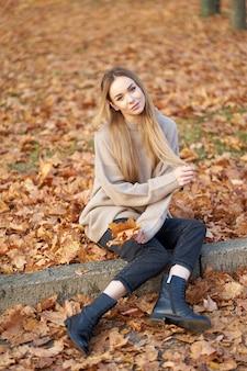 居心地の良いセーターを着て美しい長い髪の金髪美少女
