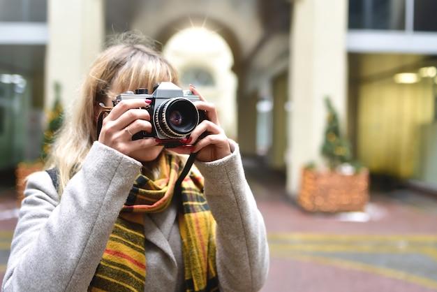 都会の古い建築物で写真を撮っている間、彼女の手にレトロなカメラを持つ金髪のかわいい写真家の女性。新しい場所を発見してください。