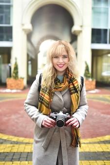 都会の古い建築物で写真を撮っている間、彼女の手にレトロなカメラを持つ金髪のかわいい写真家の女性。