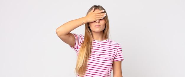 片手で目を覆っている金髪のきれいな女性は、恐怖や不安を感じ、不思議に思ったり、盲目的に驚きを待っています