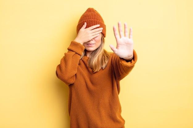 금발의 예쁜 여자는 손으로 얼굴을 가리고 다른 손을 앞에 두고 카메라를 멈추고 사진이나 사진을 거부합니다.