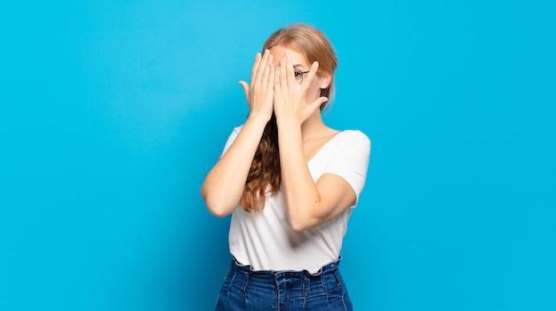 Блондинка красивая женщина закрыла лицо руками, выглядывая между пальцами с удивленным выражением лица и глядя в сторону