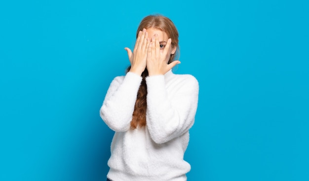 Blonde pretty woman covering face with hands, peeking between fingers with surprised expression and looking to the side