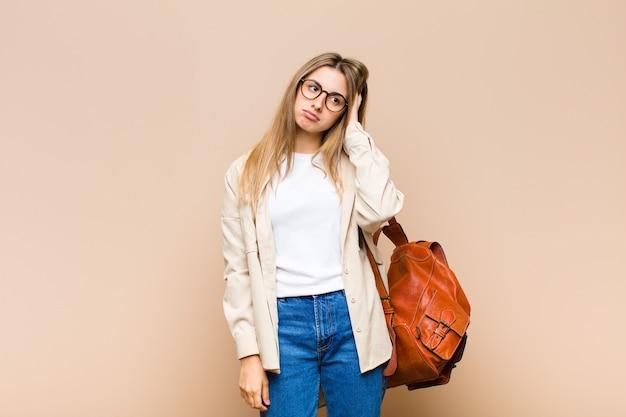 手で顔を保持し、退屈で、退屈で退屈な仕事の後に退屈、欲求不満、眠い感じの金髪のきれいな女性