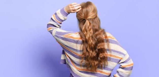 無知で混乱している金髪のきれいな女性、解決策を考えて、腰に手を、頭に他の人、背面図