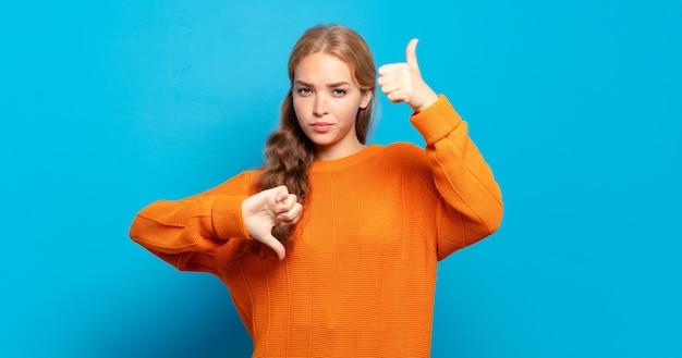 金髪のきれいな女性は、混乱し、無知で、確信が持てず、さまざまなオプションや選択肢で良い点と悪い点に重みを付けています