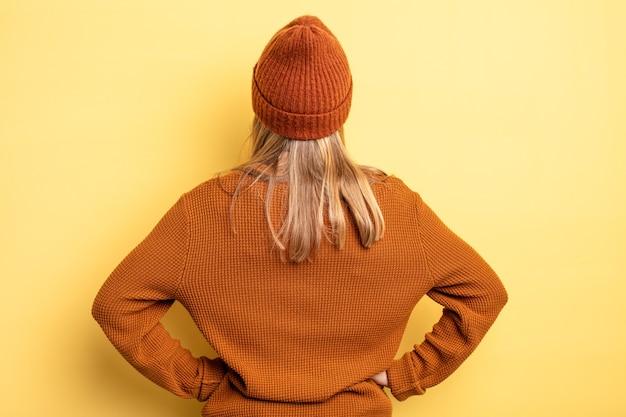 금발의 예쁜 여자는 혼란스럽거나 가득 차거나 의심과 질문을 느끼고, 엉덩이에 손을 얹고, 후면을 봅니다.