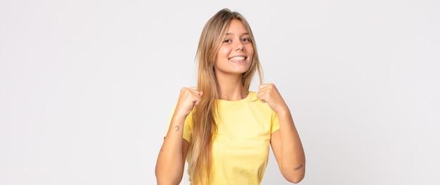 幸せと恋を感じている金髪のきれいな女性は、片方の手が心臓の横にあり、もう一方の手が前に伸びて笑っている
