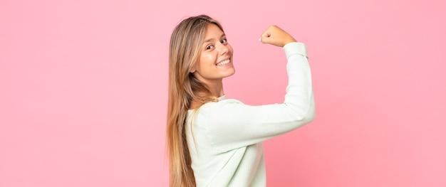 幸せ、満足、パワフル、屈曲フィットと筋肉の上腕二頭筋を感じ、ジムの後に強く見える金髪のきれいな女性