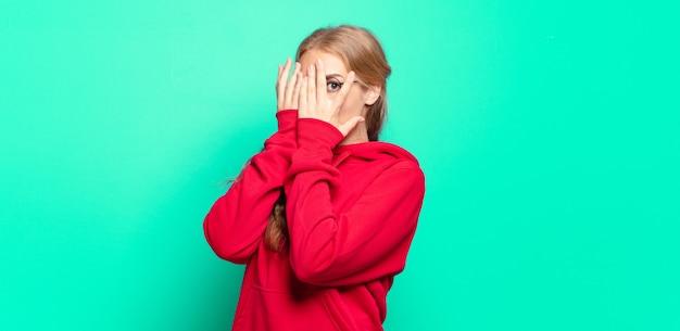 Блондинка красивая женщина чувствует себя напуганной или смущенной, подглядывает или шпионит с полузакрытыми руками глазами
