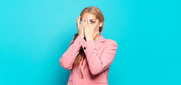 Блондинка красивая женщина чувствует себя напуганной или смущенной, подглядывает или шпионит глазами, наполовину прикрытыми руками