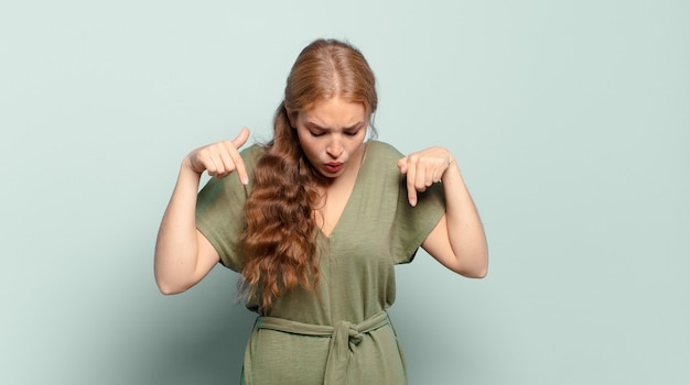 금발의 예쁜 여자가 충격을 받고 입을 벌리고 놀란 느낌, 불신과 놀라움에서 아래쪽을 가리키고 가리키는