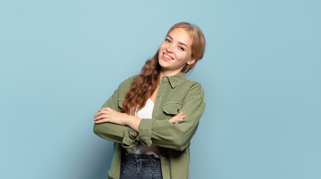 Blonde pretty woman laughing happily with arms crossed, with a relaxed, positive and satisfied pose