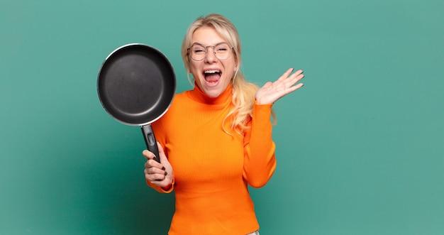 Блондинка красивая женщина учится готовить с кастрюлей