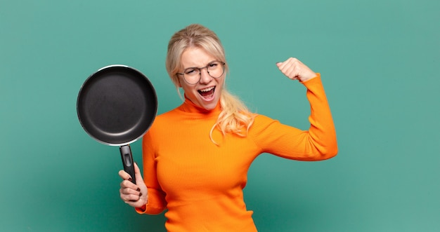 Blonde pretty woman learning cook with a pan