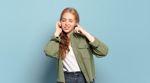 금발의 예쁜 여자는 화가 나고 스트레스를 받고 짜증이 나서 귀를 듣지 못하는 소음, 소리 또는 시끄러운 음악에 양쪽 귀를 덮고 있습니다.