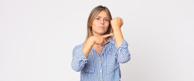頭痛と片方の手が顔の半分を覆っている、眠くて退屈であくびをしている金髪のきれいな女性