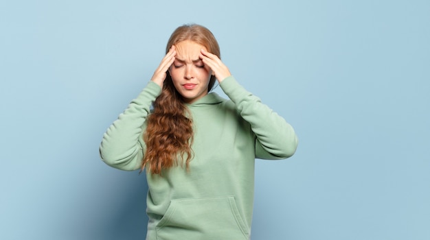 Блондинка красивая женщина выглядит напряженной и расстроенной, работает под давлением с головной болью и обеспокоена проблемами