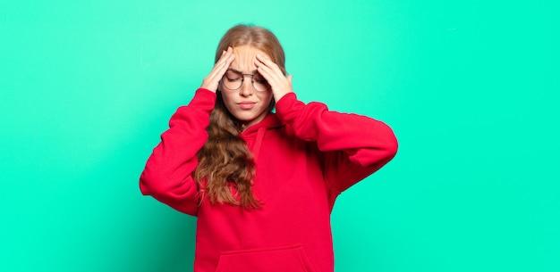 금발의 예쁜 여자는 스트레스와 좌절감을 느끼고 두통으로 압력을 받고 문제를 겪고 있습니다.