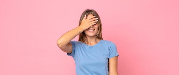 Блондинка красивая женщина выглядит напряженной, пристыженной или расстроенной, с головной болью, закрывая лицо рукой