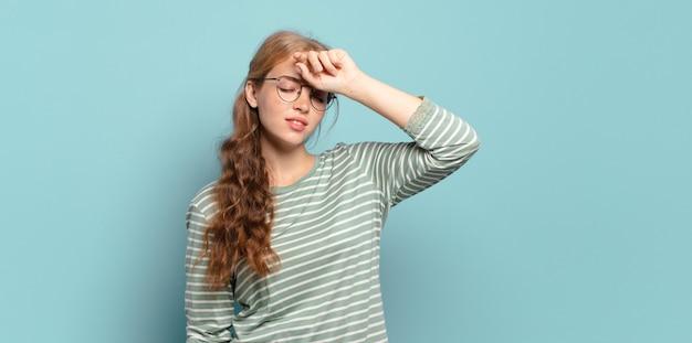 ストレス、疲れ、欲求不満を見て、額から汗を乾かす金髪のきれいな女性