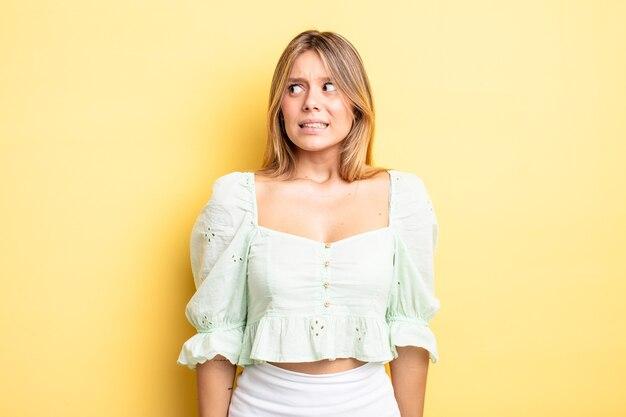 心配、ストレス、不安、恐怖、パニック、歯を食いしばっている金髪のきれいな女性