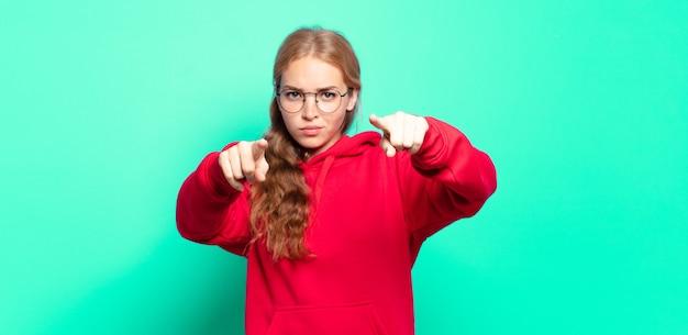 금발의 예쁜 여자가 손가락과 화난 표정으로 카메라를 앞으로 가리키며 의무를 다하라고 말합니다.