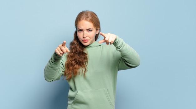 손가락과 화난 표정으로 앞으로 가리키는 금발의 예쁜 여자, 당신의 의무를 다하라고 말합니다.