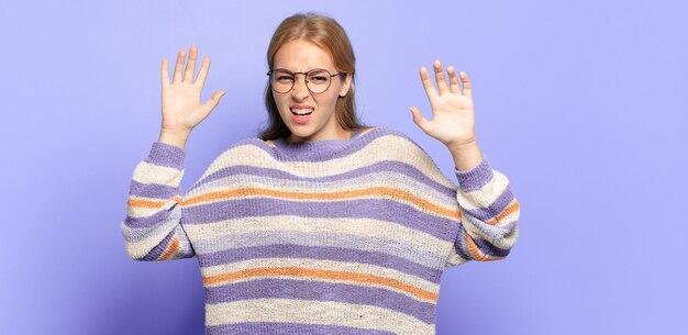Блондинка красивая женщина кричит в панике или гневе, шокирована, испугана или разъярена, с руками рядом с головой