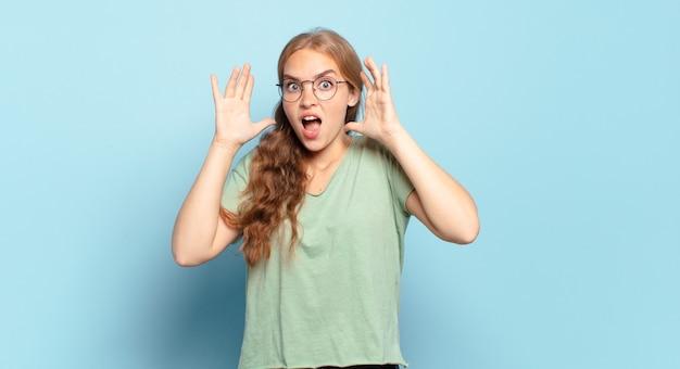 空中で手を上げて叫んで、激怒、欲求不満、ストレス、動揺を感じている金髪のきれいな女性
