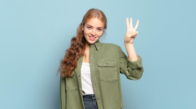 笑顔でフレンドリーに見える金髪のきれいな女性、前に手を前に3番目または3番目を示し、カウントダウン