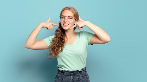 自信を持って笑顔の金髪のきれいな女性は、自分の広い笑顔、前向きで、リラックスした、満足のいく態度を指しています