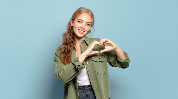 Blonde pretty woman smiling and feeling happy, cute, romantic and in love, making heart shape with both hands