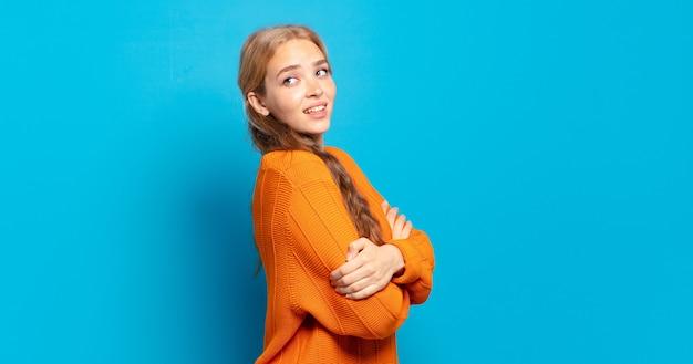 嬉しそうに笑って、幸せで、満足して、リラックスして、腕を組んで、横を向いている金髪のきれいな女性