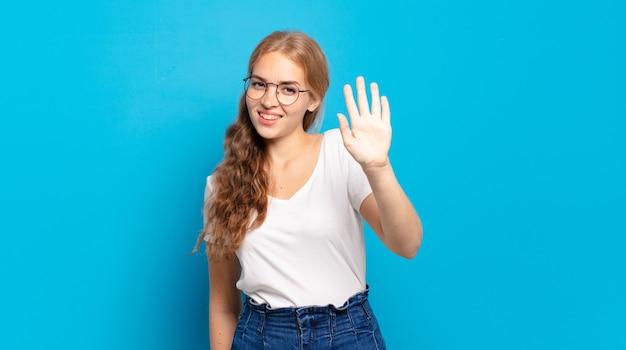 幸せにそして元気に笑って、手を振って、あなたを歓迎して挨拶するか、さようならを言う金髪のきれいな女性