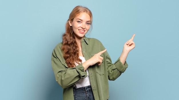Блондинка красивая женщина счастливо улыбается и указывает в сторону и вверх обеими руками, показывая объект в пространстве для копирования
