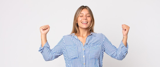 Блондинка красивая женщина счастливо улыбается и указывает в сторону и вверх обеими руками, показывая объект в копировальном пространстве