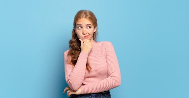 Блондинка красивая женщина думает, чувствуя себя сомнительно и смущенно, с разными вариантами, задаваясь вопросом, какое решение принять